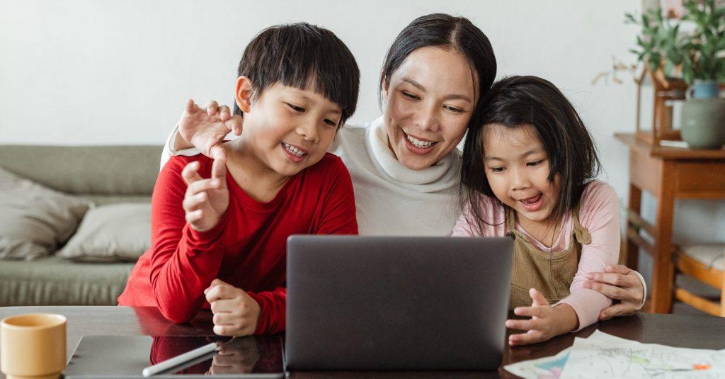 Mutter mit zwei Kindern sitzen vor einem Laptop